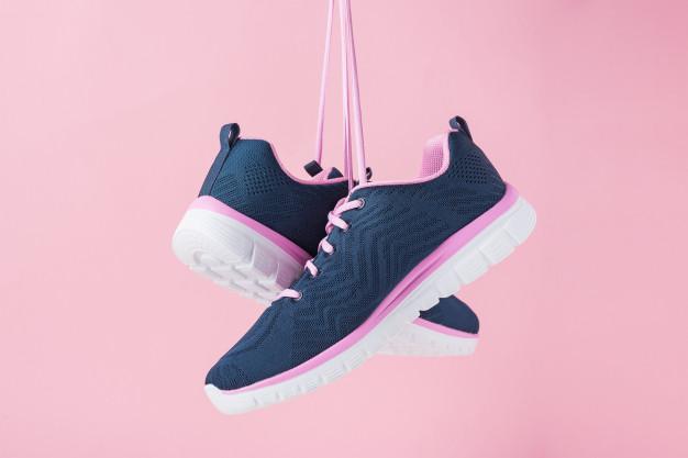 Αθλητικά παπούτσια στον αέρα με ροζ φόντο