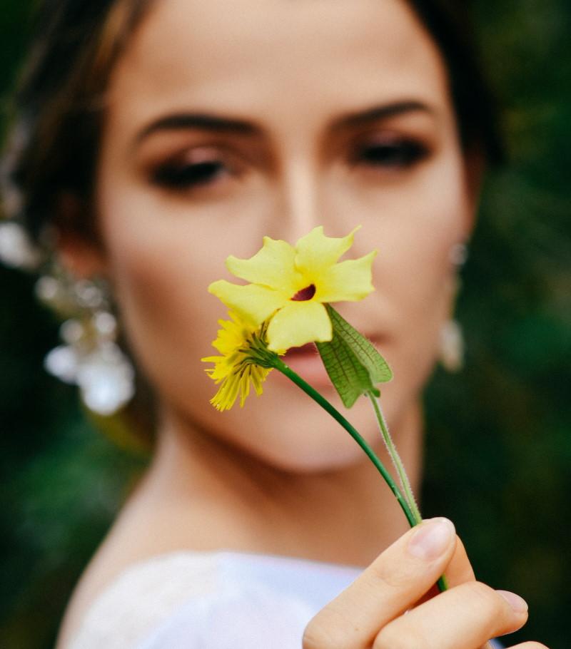 Γυναίκα με σκουλαρίκια κρατάει λουλούδι
