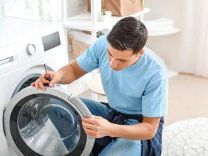 Τεχνικός κοιτάει πόρτα κάδου πλυντηρίου