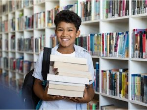 Παιδί κρατάει χαμογελώντας στοίβα βιβλίων