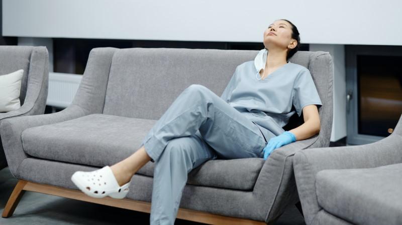 Νοσοκόμα καθισμέη σε καναπέ με ρούχα εργασίας και σαμπό